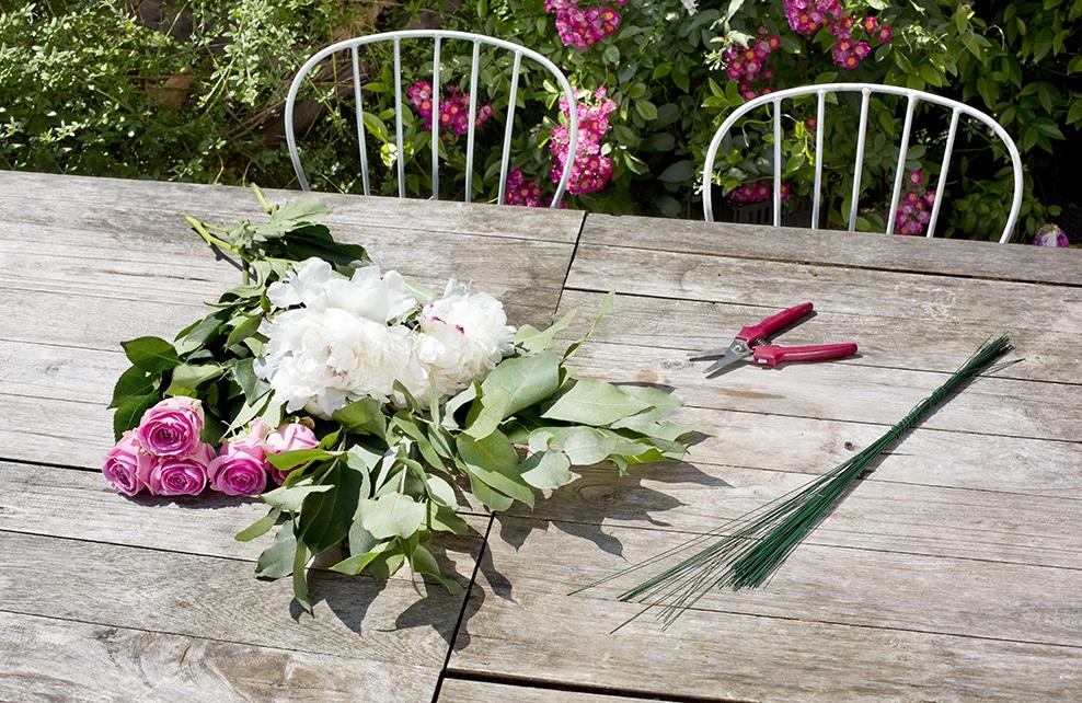 fleur et feuillages sur table en bois, roses, sécateur, chaise de jardin