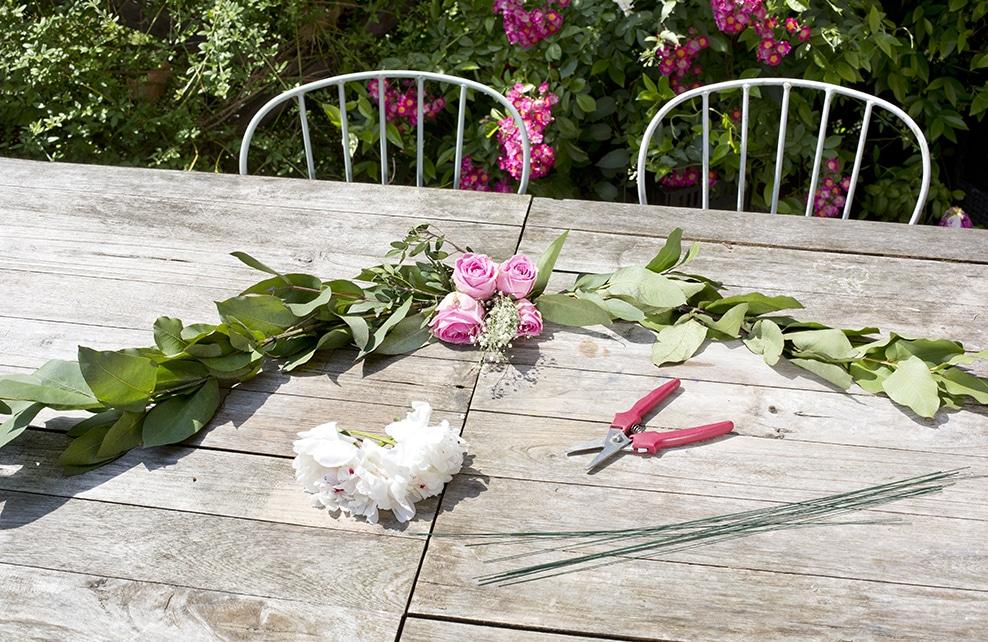 fleur et feuillage sur table en bois, roses, sécateur, chaise de jardin