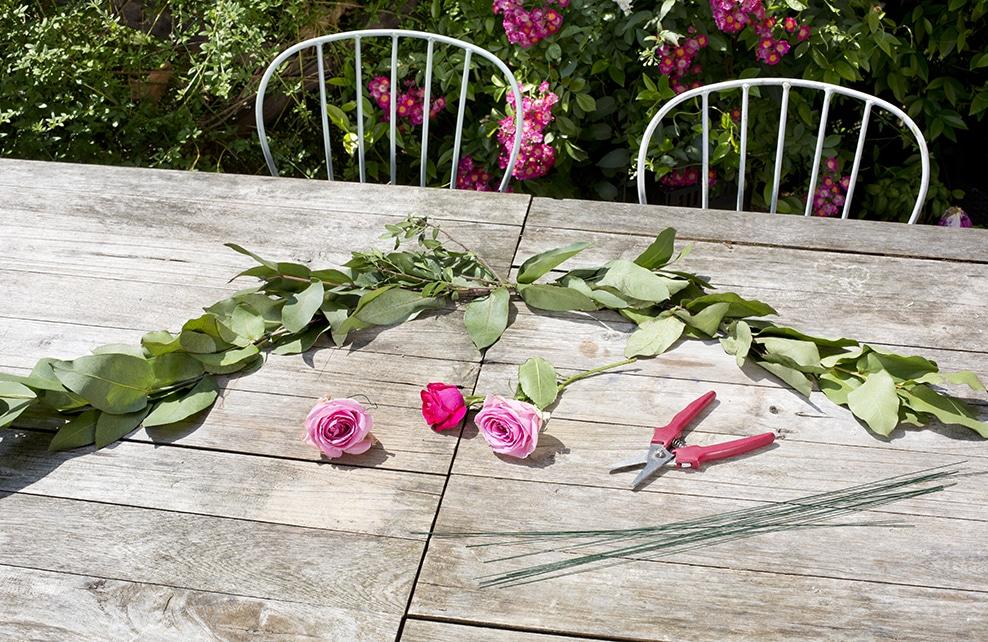 fleur et feuillage sur table en bois, rose, sécateur, chaise de jardin
