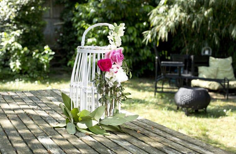 lanterne décorée avec fleurs sur table en bois dans un jardin