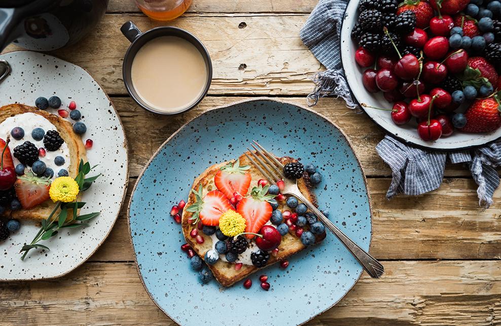 petit déjeuner avec tartine agrémenté de fruit, bol de fruit, cerises, mure, groseille, tasse de café