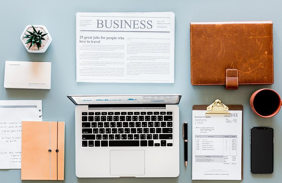 bureau très bien rangé avec ordinateur bloc-notes, stylo, mug de café, journal