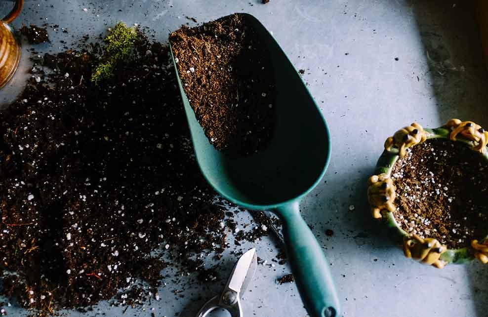 Pelle de jardin en métal vert remplie de terre brune