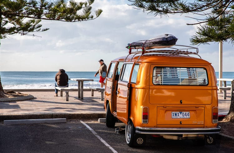 van Volkswagen orange sur bord de mer garé sur un parking