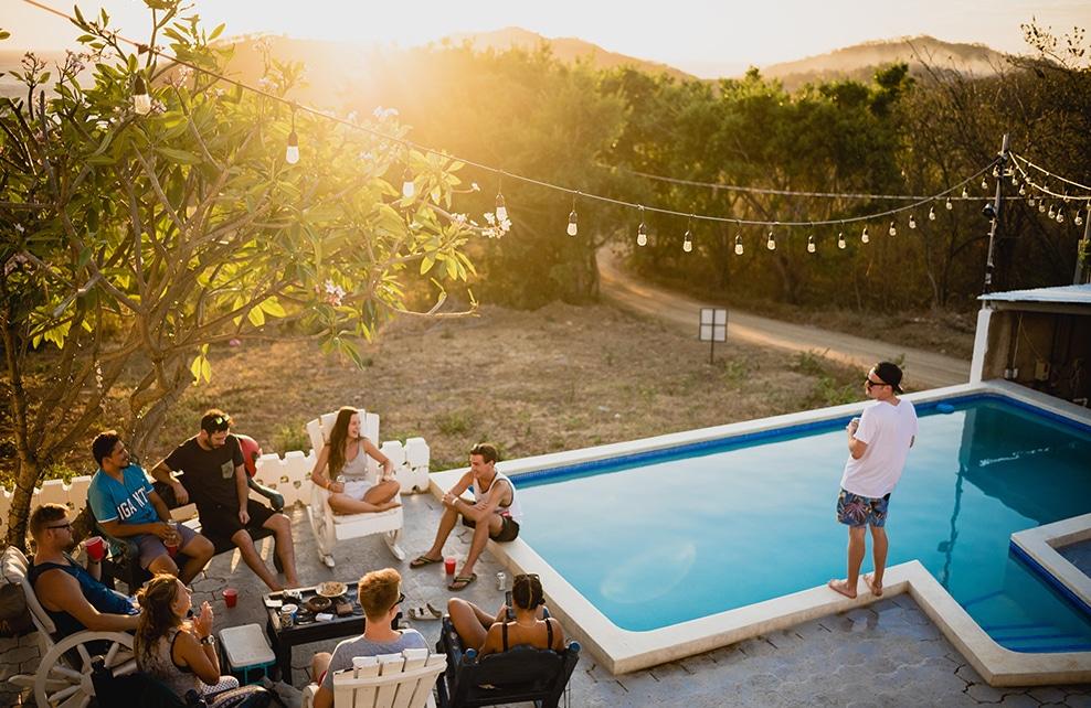 maison avec piscine et des gens autour d'un salon d'extérieur