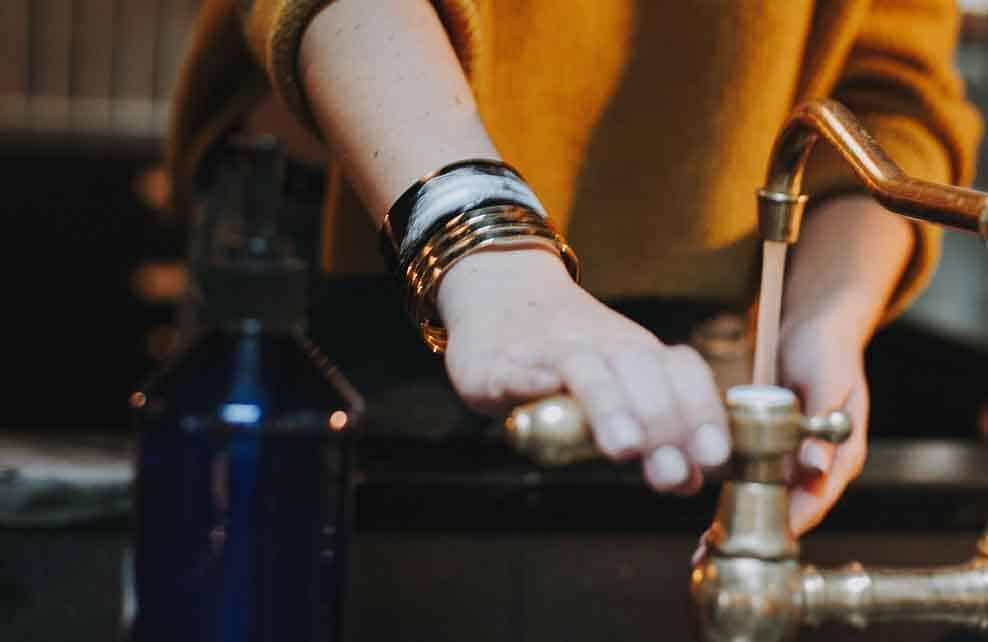 Femme fermant le robinet d'eau