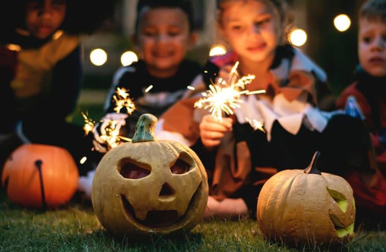 Enfants allumant des lanternes dans des citrouilles pour Halloween