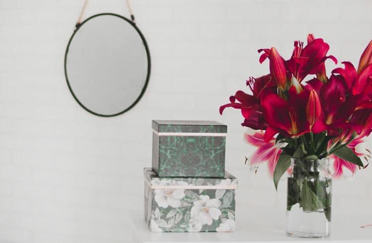 Boites posées sur un buffet à côté d'un bouquet de fleurs et un miroir