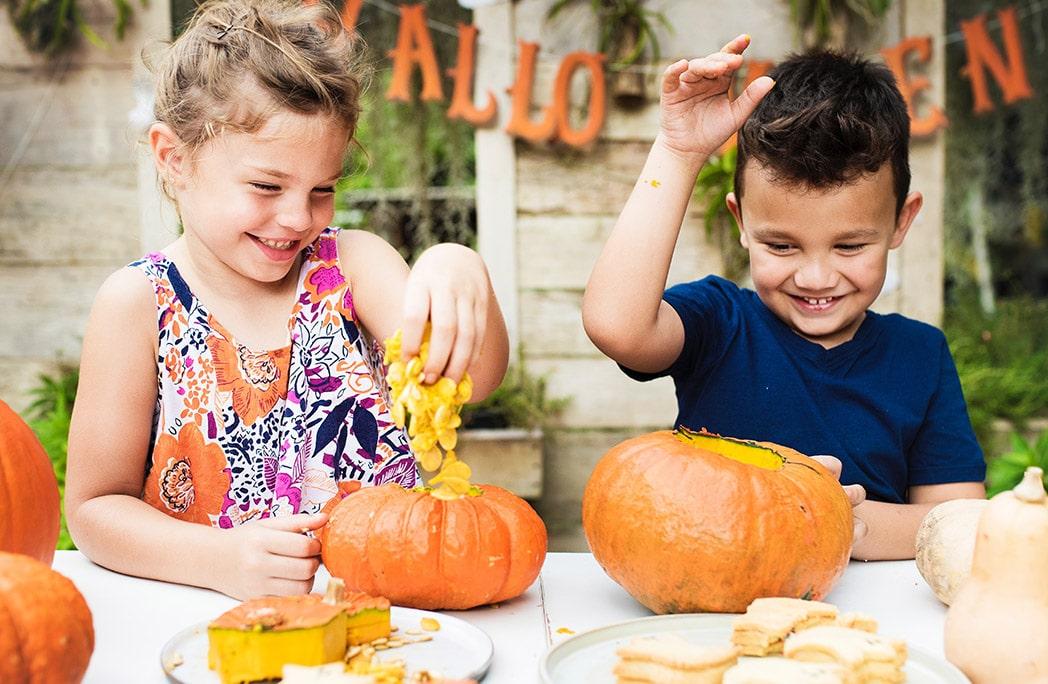Deux enfants en train de faire une activité citrouille pour Halloween