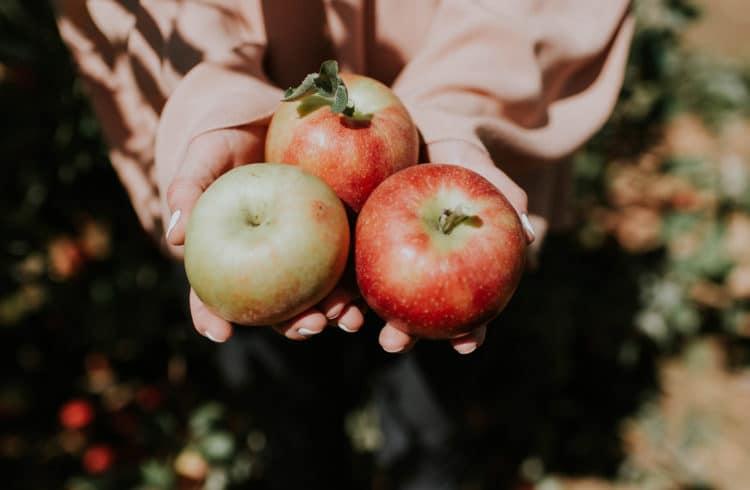 Jeune femme tenant 3 pommes dans ses mains