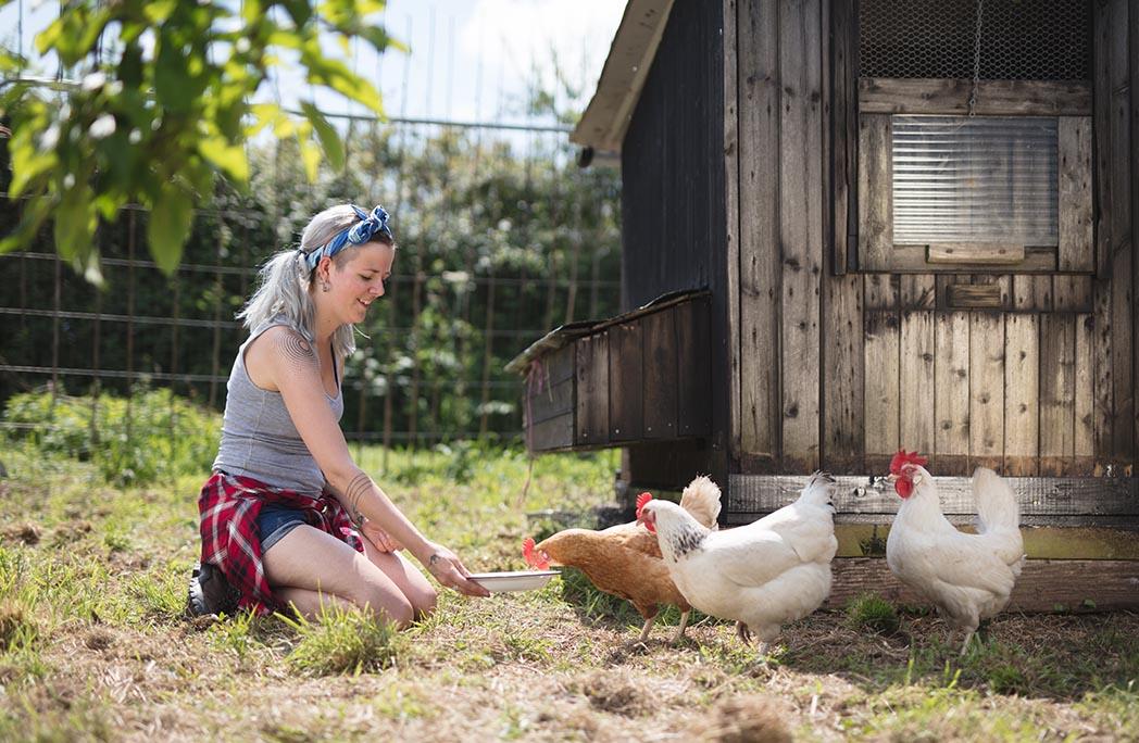 Jeune femme nourrissant les poules