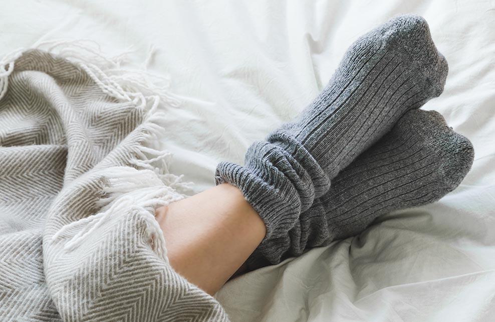 Pieds avec des chaussettes qui dépassent d'une couverture