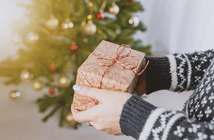 Mains de femme portant un cadeau à Noël