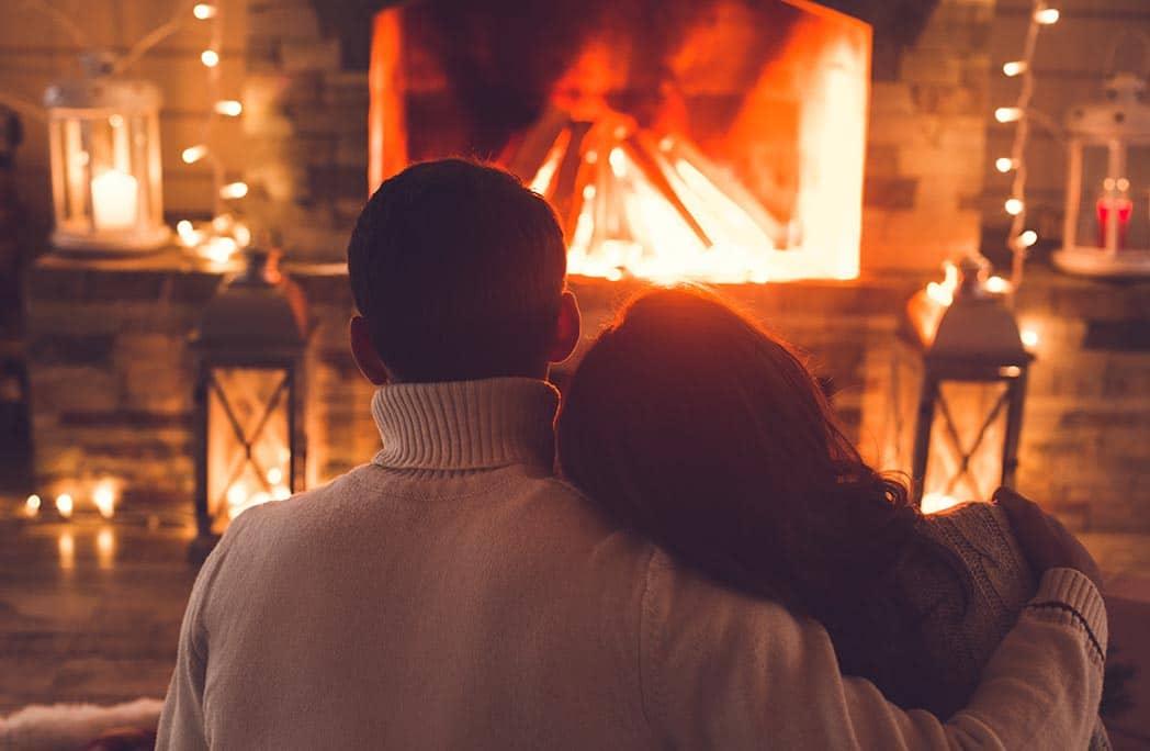 Couple s'enlacant devant un feu de cheminée