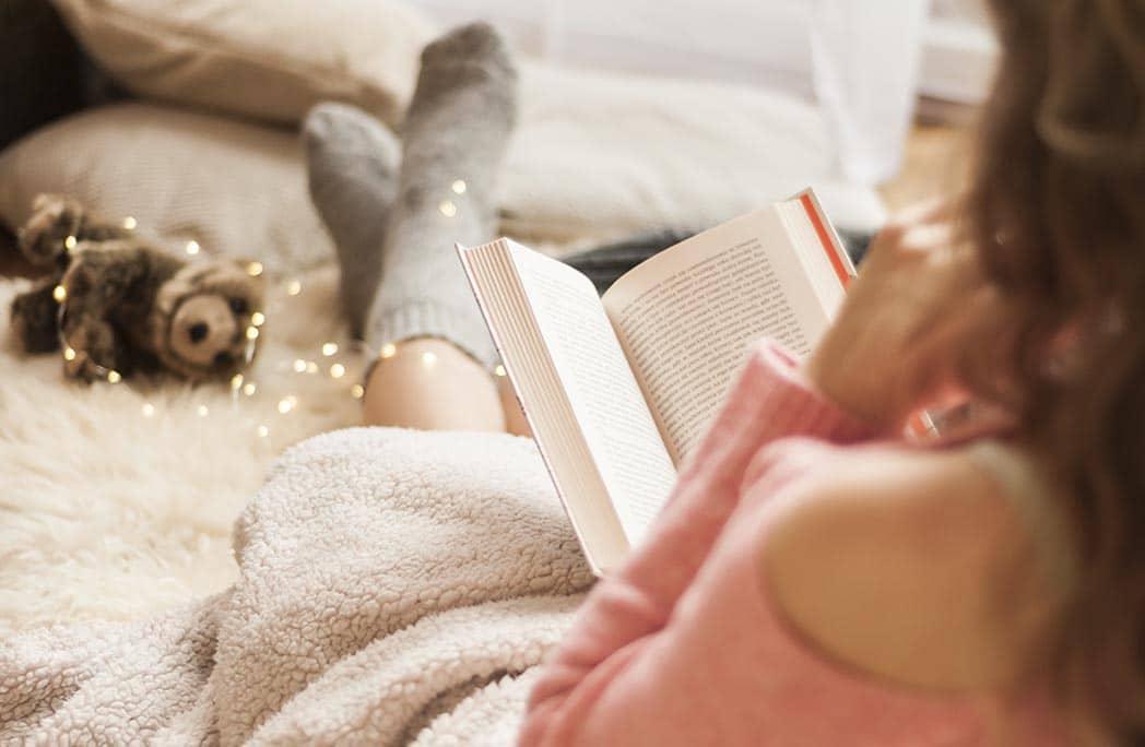 Femme lisant un livre enroulée dans une couverture sur un lit