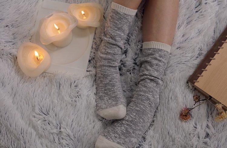 PIeds d'une jeune femme dans des chaussettes sur un lit avec des bougies