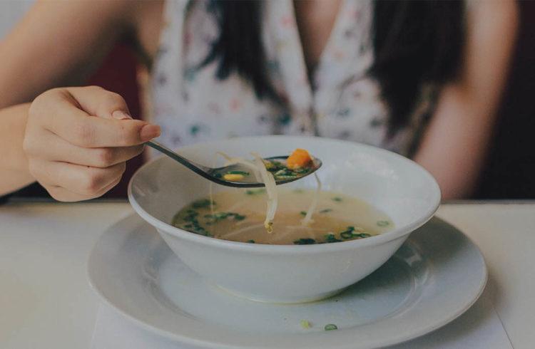 Jeune femme dégustant une soupe de légumes