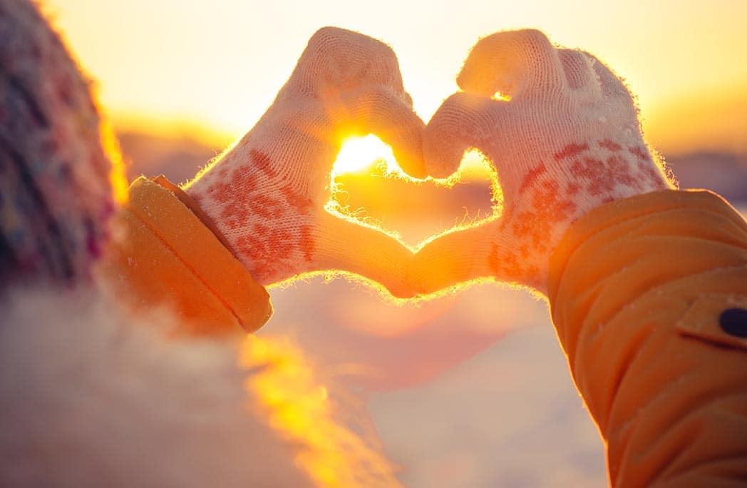Jeune femme en hiver faisant un coeur avec ses doigts
