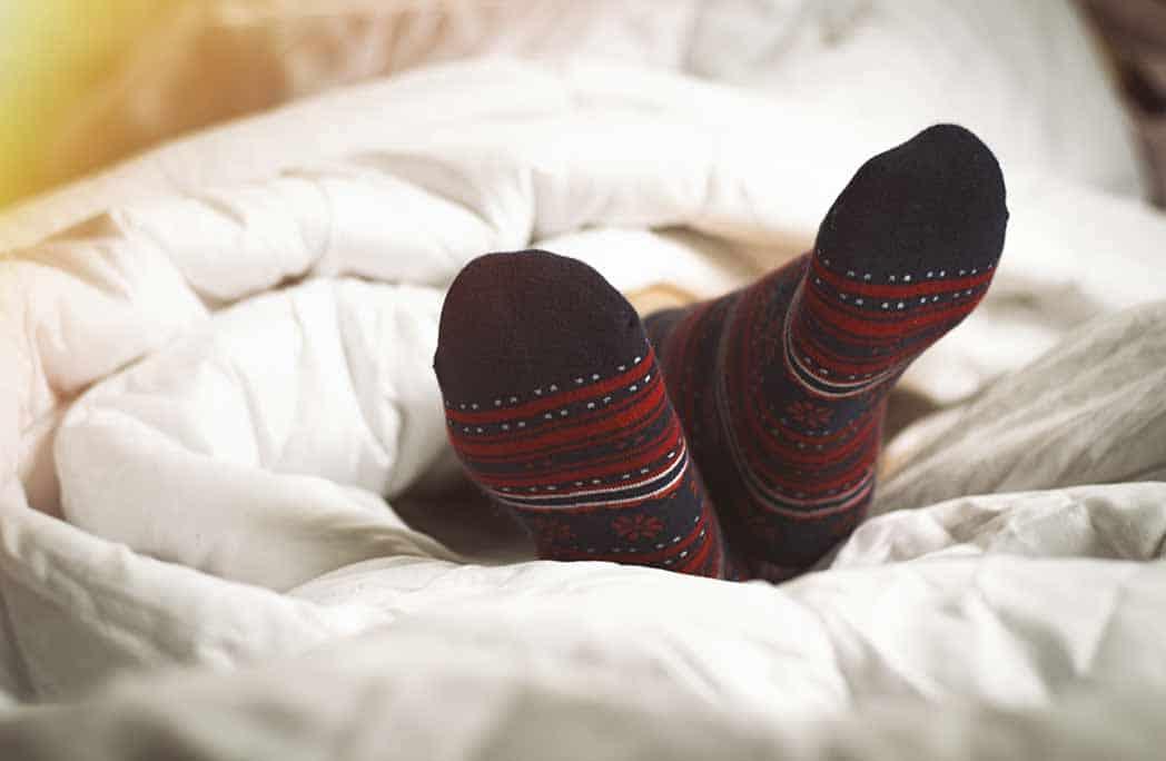 Pieds en chaussettes d'hiver dépassant de la couette