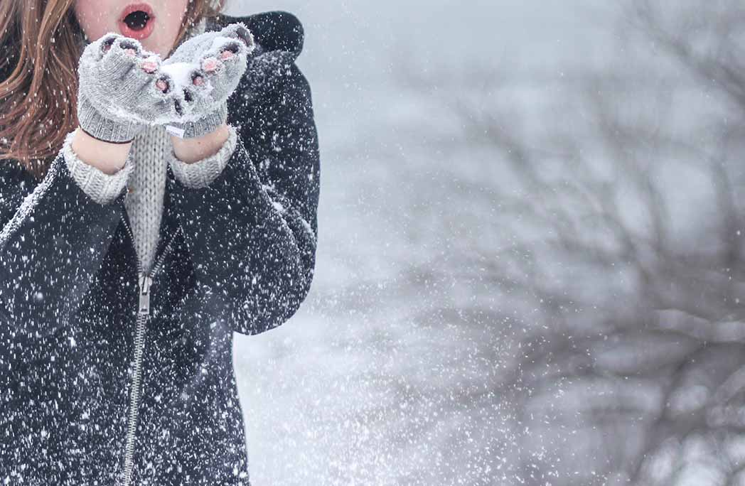 Jeune femme soufflant dans la neige