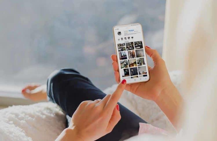 Femme assise sur un canapé en train de regarder Instagram sur son téléphone