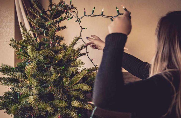 Femme defaisant son sapin de Noël