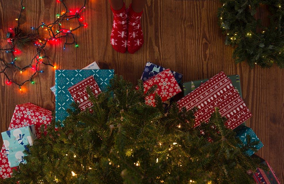 Cadeaux au pied d'un sapin et pieds en chaussettes d'une jeune fille