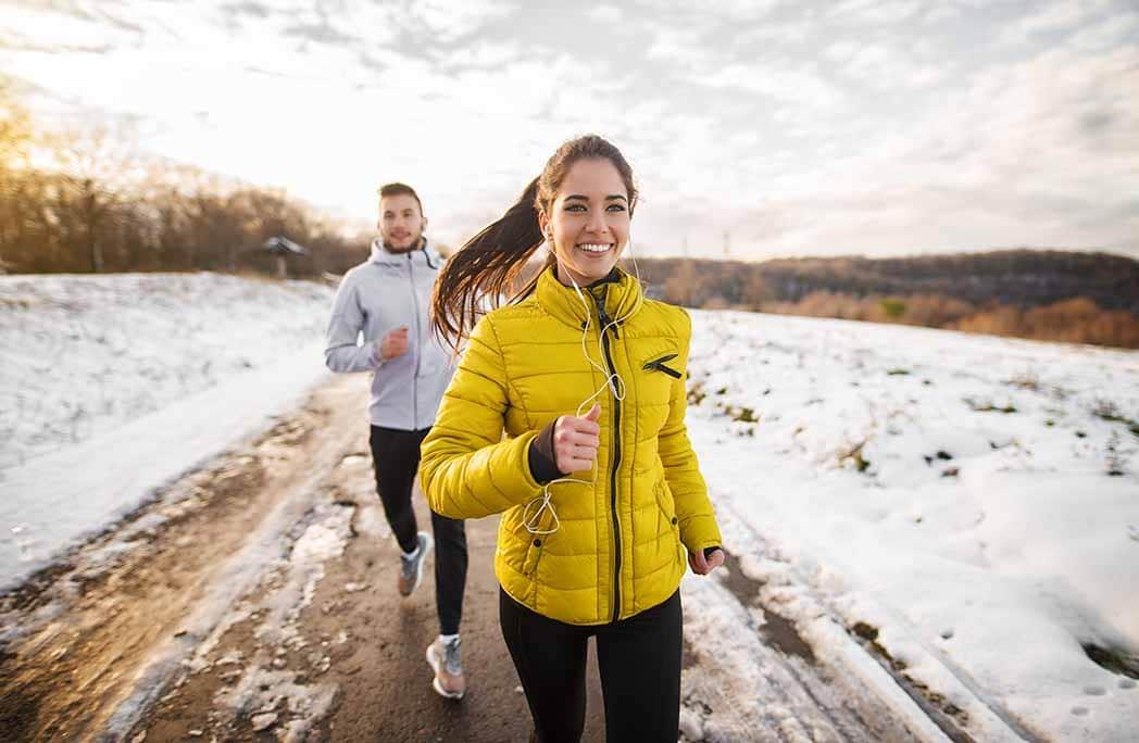 Jeune femme et jeune homme qui courent l'hiver