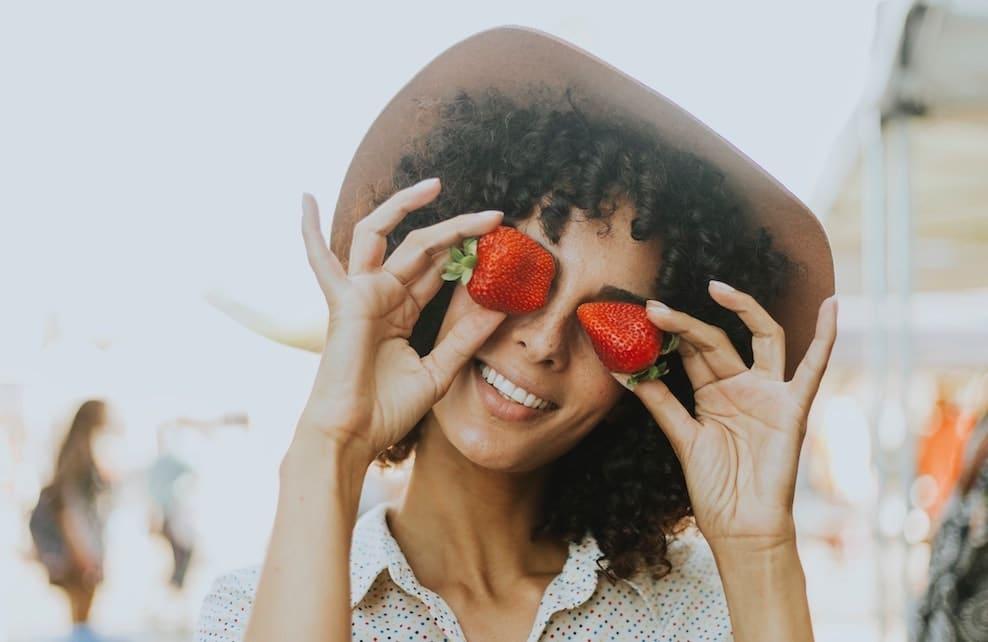 Femme qui mets des fraises devant ses yeux