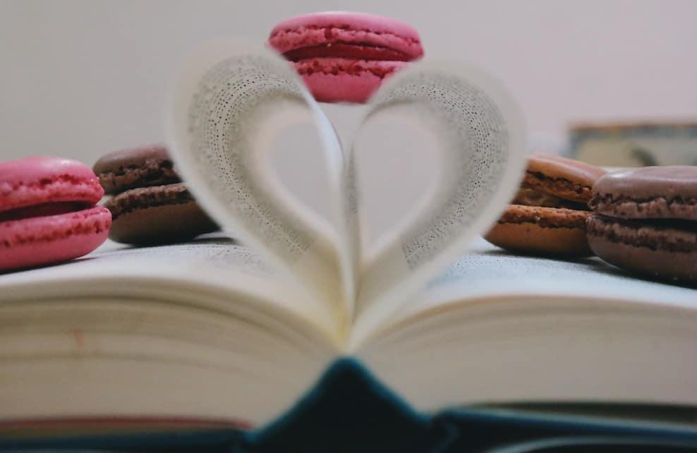 Macaron posé sur deux pages formant un coeur