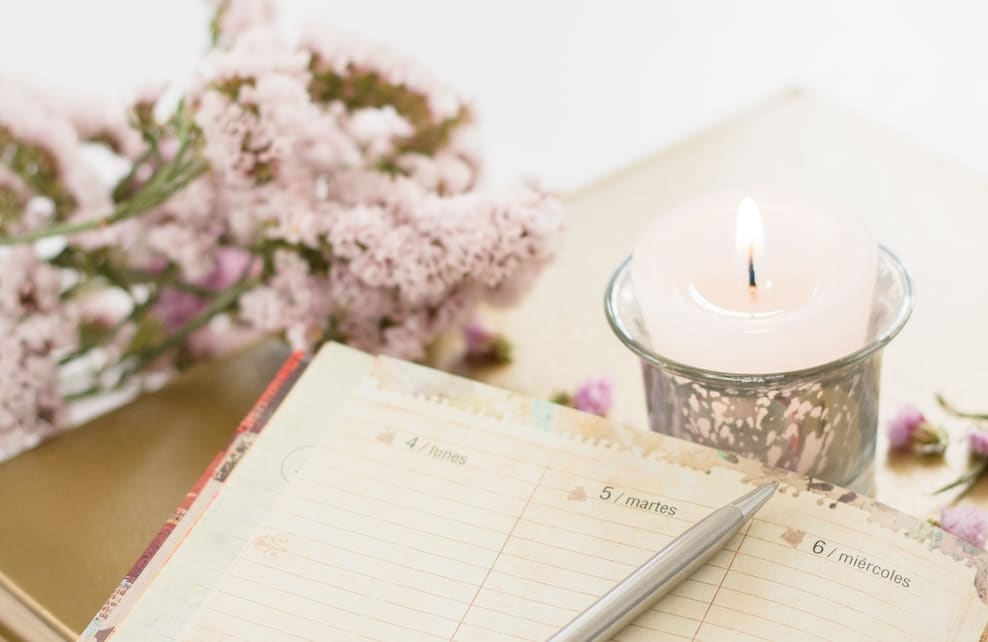 Bougie allumée posée à coté d'un agenda et d'un bouquet de fleurs