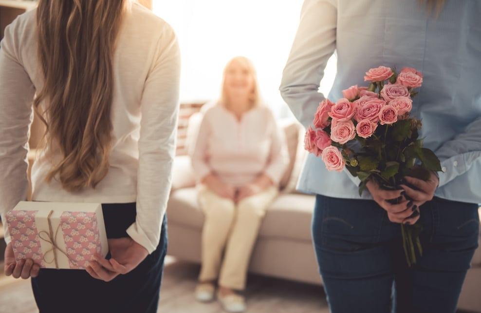 Petites-filles tenant un cadeau et un bouquet de fleurs pour leur grand-mère