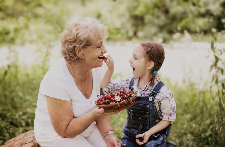 Grand-mère et sa petite-fille mangeant des cerises dans un jardin
