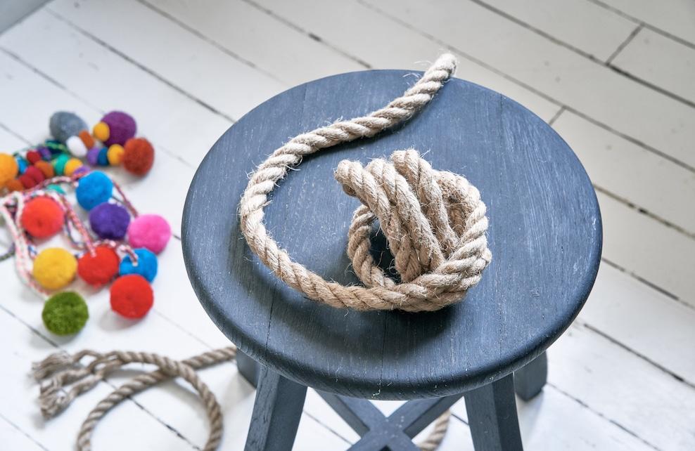 Corde de raffia posée sur un tabouret noir en bois
