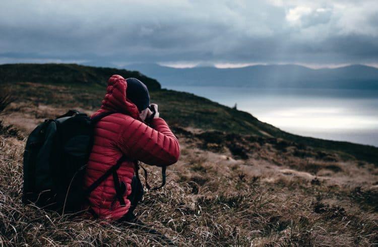 Photographe assis dans de l'herbe séchée, photographiant un lac