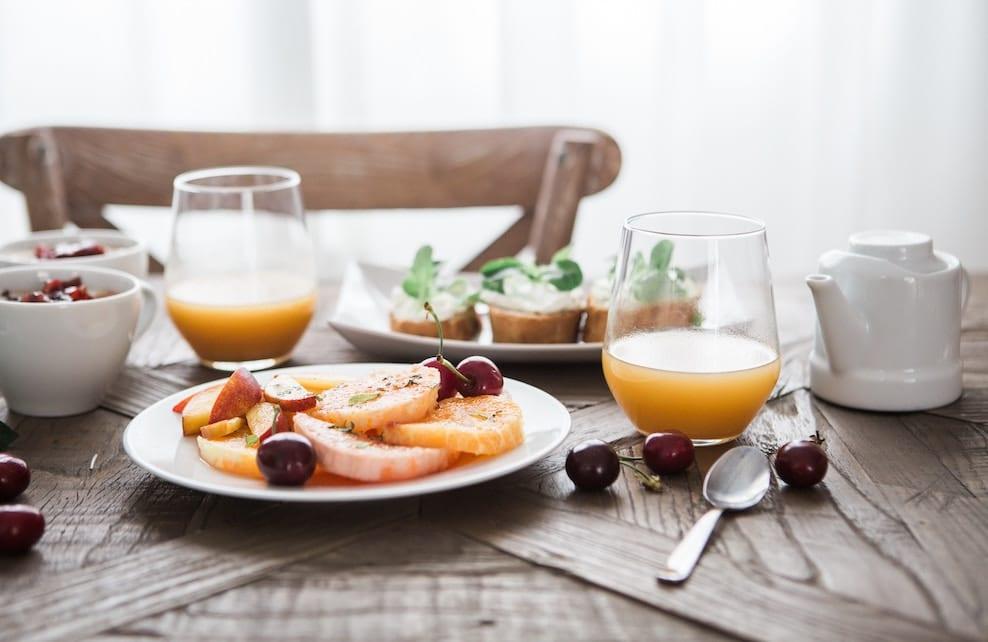 Tranches de fruit sur une assiette et verres de jus