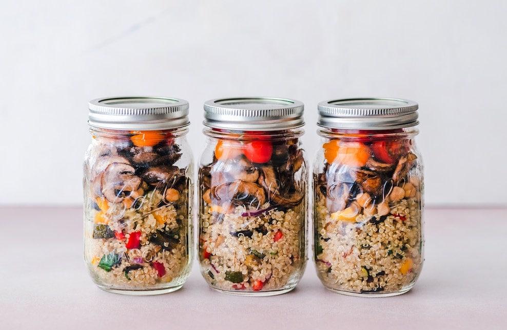 3 bocaux en verres contenant du quinoa et des légumes