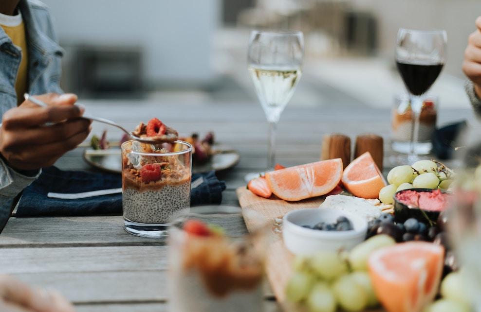 Focus sur une table, deux personnes en train de déguster des verrines avec du vin et du champagne