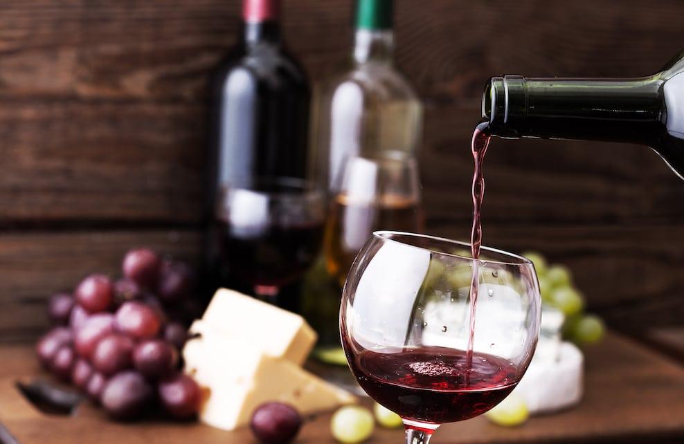 Bouteille de vin rouge et verre avec du fromage et du raisin en arrière plan
