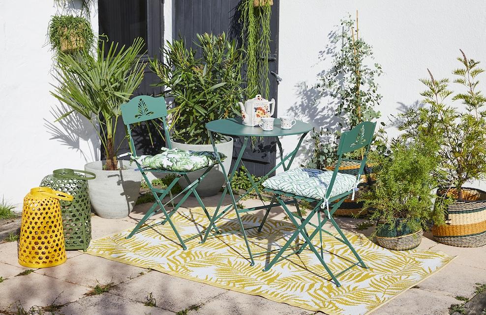 Terrasse avec une table et des chaises entourées de plantes vertes