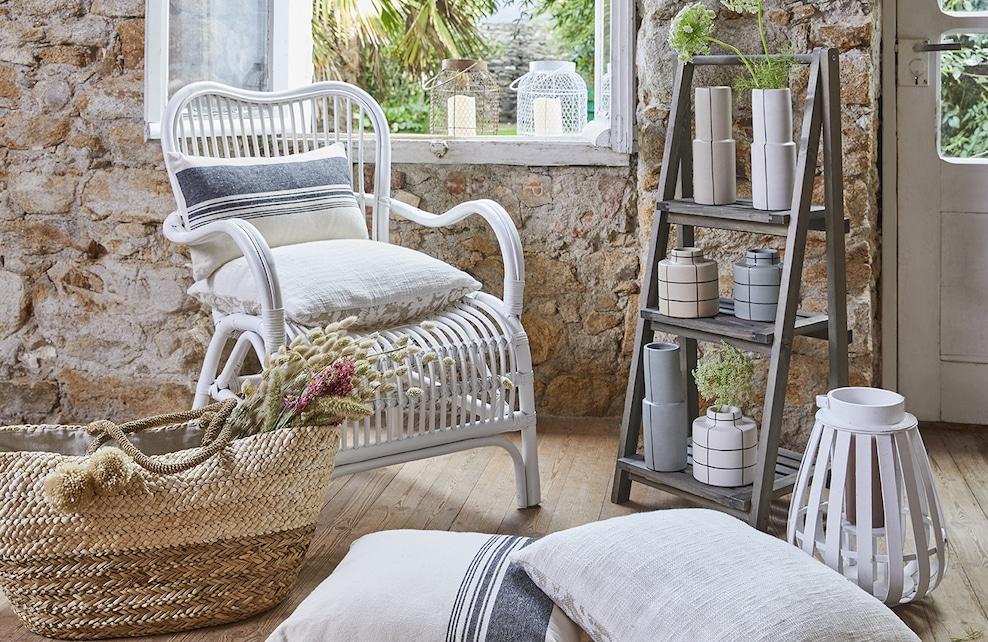 Photo d'ambiance avec fauteuil en rotin, coussins et vases ethniques