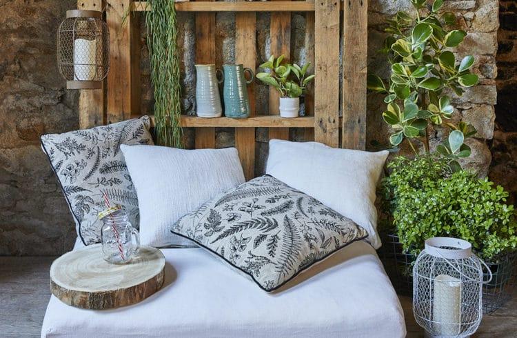 Coin détente décoré avec des coussin à imprimés floraux, des vases et des plantes vertes