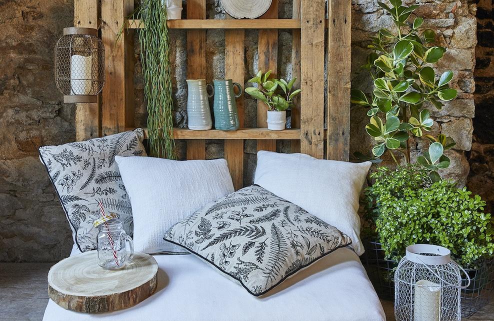 Coin détente décorée avec des coussin à imprimés floraux, des vases et des plantes vertes