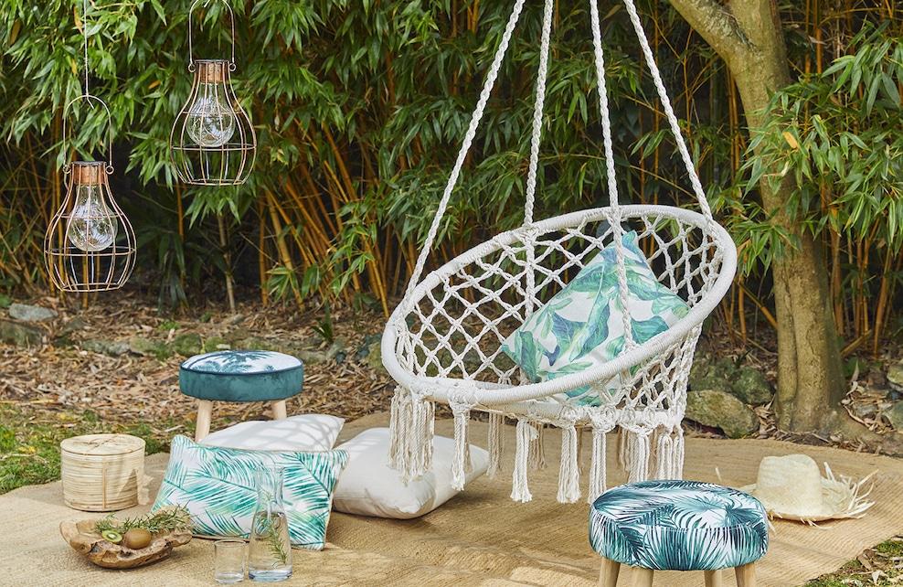 Coin détente dans le jardin avec un fauteuil suspendu deux tabourets aux motifs jungle et les coussins assortis
