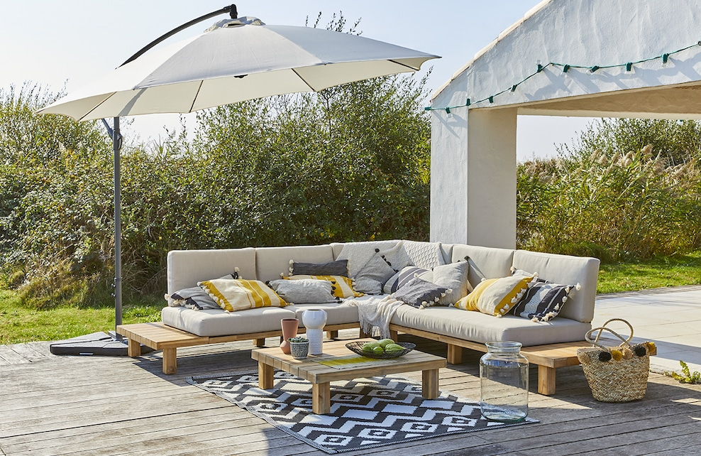 Salon de jardin avec son parasol, son canapé et une table basse