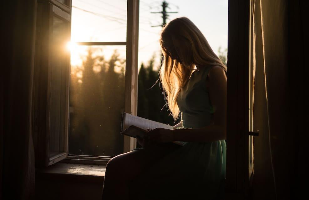 Jeune fille lisant un livre sur un rebord de fenêtre