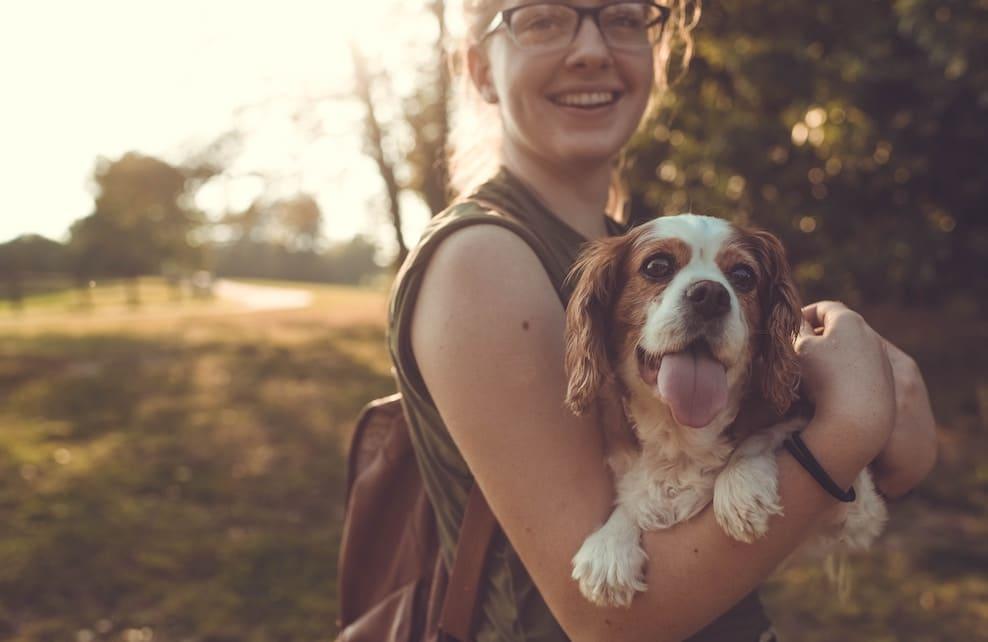 Jeune femme tenant un chien dans les bras