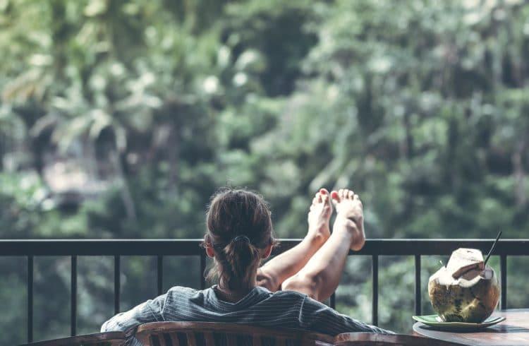 Femme se prélassant sur sa terrasse au vert