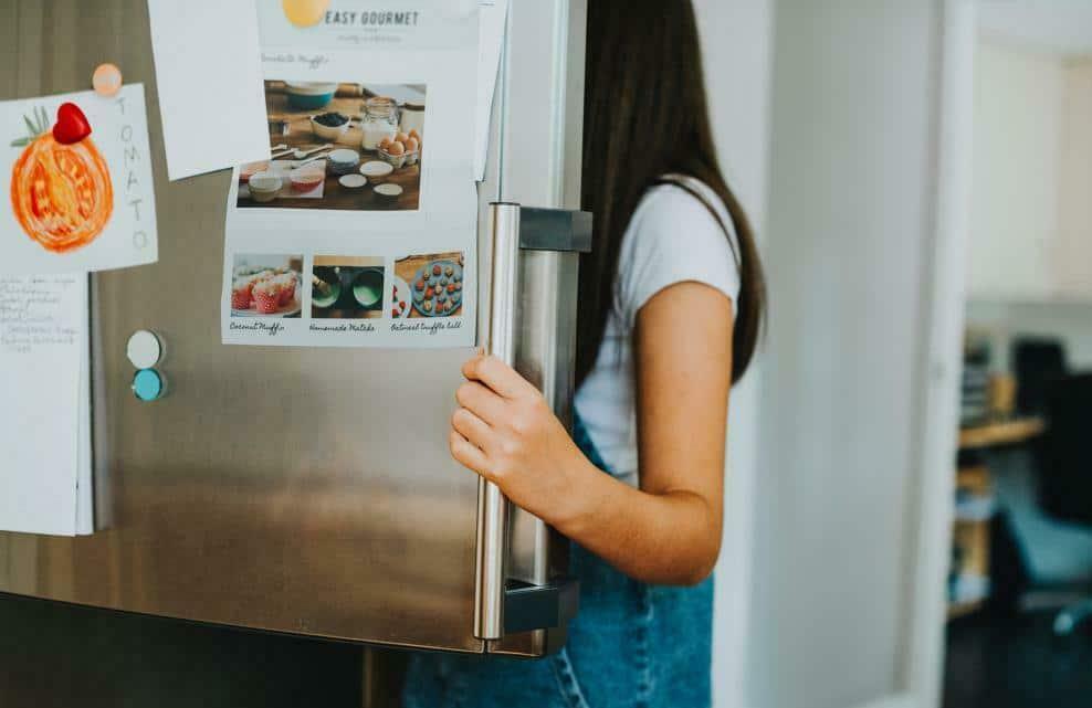 Une femme ouvre un réfrigérateur